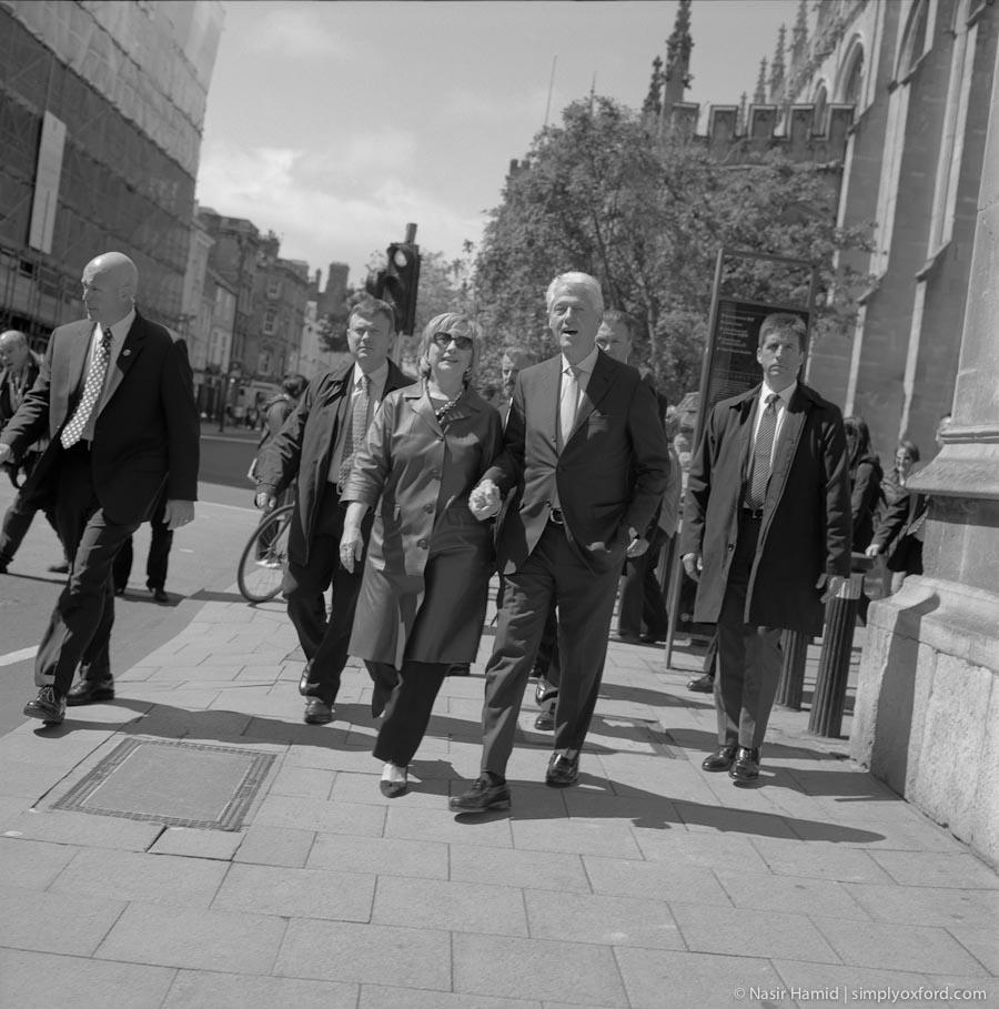 Bill and Hillary Clinton walking along Oxford High Street